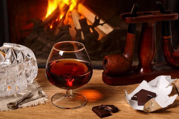 Kieliszek brandy, fajki czekoladowe i tytoniowe na dębowym stole na tle płonącego kominka