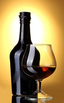 Kieliszek brandy i butelka na żółtym tle