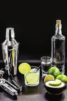 Kieliszek caipirinha z naczyniami barowymi. typowy brazylijski napój z cytryny na czarnym stole