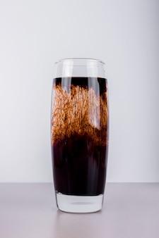 Kieliszek ciemnego koktajlu.