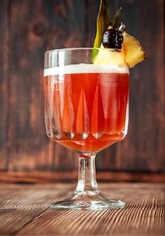 Kieliszek club cocktail przyozdobiony kawałkiem ananasa i wiśnią maraschino
