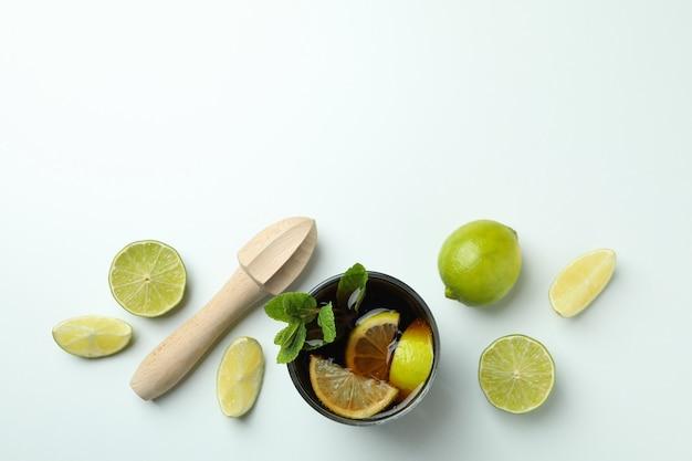 Kieliszek cuba libre, limonki i drewniana sokowirówka na białej powierzchni, widok z góry