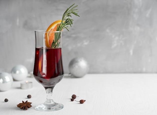 Kieliszek czerwonego grzanego wina z plastrami pomarańczy i rozmarynem z bombkami na drewnianym stole