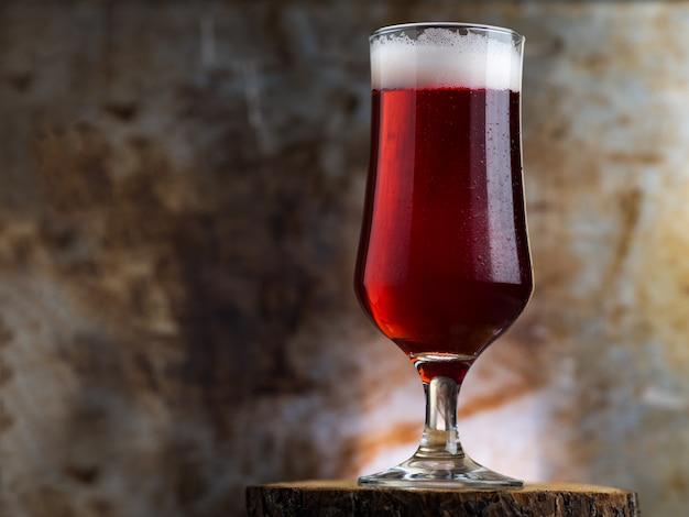 Kieliszek czerwonego piwa na ciemnym tle metalu