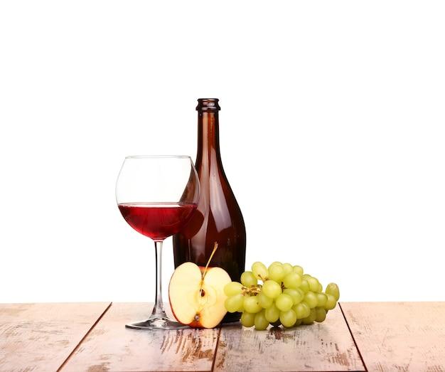 Kieliszek czerwonego wina, butelka wina i winogrona jabłko na pokładzie na białym tle