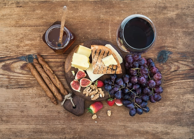 Kieliszek czerwonego wina, deska serów, winogron, figi, truskawek, miodu i paluszki na rustykalnym drewnianym stole