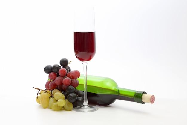 Kieliszek czerwonego wina i butelka z winogronami na białym tle
