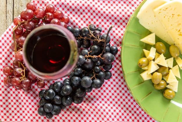 Kieliszek czerwonego wina i kiść winogron.