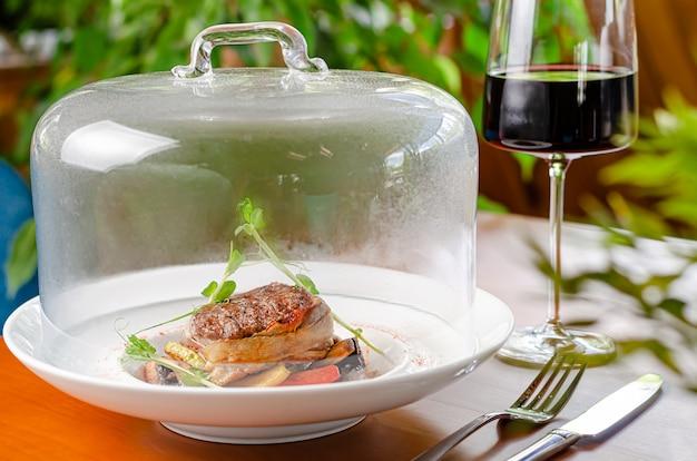 Kieliszek czerwonego wina i medalion cielęcy z warzywami pod przezroczystym wieczkiem. restauracja serwująca danie