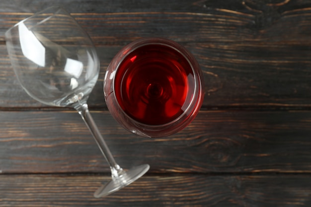 Kieliszek czerwonego wina i pusty kieliszek na rustykalnym drewnianym tle