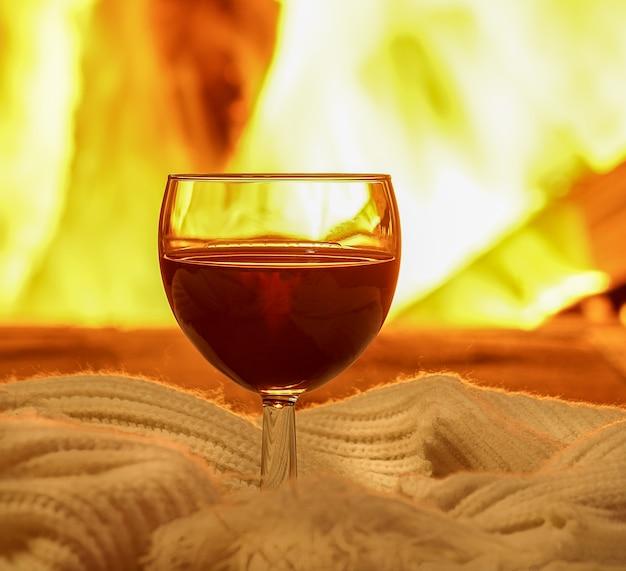 Kieliszek czerwonego wina i rzeczy z wełny w pobliżu przytulnego kominka.