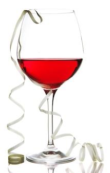 Kieliszek czerwonego wina i serpentyna po imprezie na białym tle