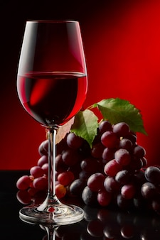Kieliszek czerwonego wina i winogron na błyszczącym stole.