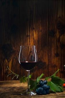 Kieliszek czerwonego wina i zbliżenie winorośli.