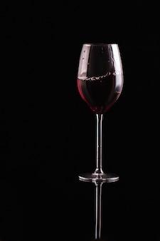 Kieliszek czerwonego wina na czarnym tle. aromatyczne wino. surowy styl. wino w ciemności