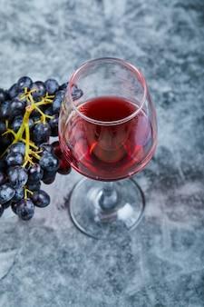 Kieliszek czerwonego wina na marmurze z winogronami.