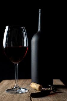 Kieliszek czerwonego wina na rustykalnym drewnianym stole, obok korkociąg i niewyraźna butelka wina