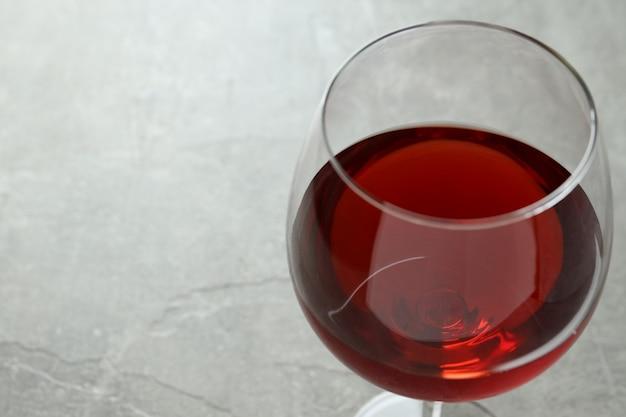 Kieliszek czerwonego wina na szarym tle z teksturą