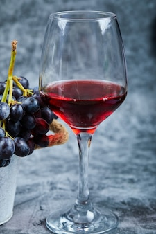Kieliszek czerwonego wina na tle marmuru z winogronami. wysokiej jakości zdjęcie