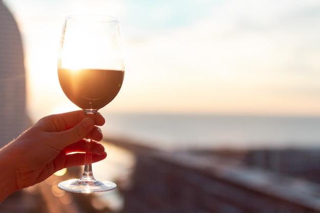 Kieliszek czerwonego wina o zachodzie słońca.