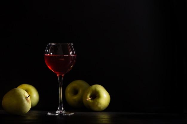 Kieliszek czerwonego wina owocowego na czarnym tle. jabłka świeże uprawy, martwa natura w niskim tonacji. skopiuj miejsce