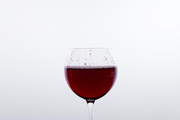 Kieliszek czerwonego wina przed białą ścianą