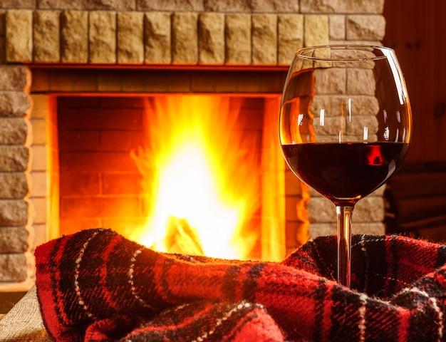 Kieliszek czerwonego wina przed przytulnym kominkiem.