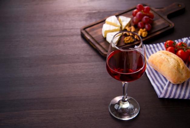 Kieliszek czerwonego wina, sera, winogron, orzechów włoskich na drewnianej desce do krojenia