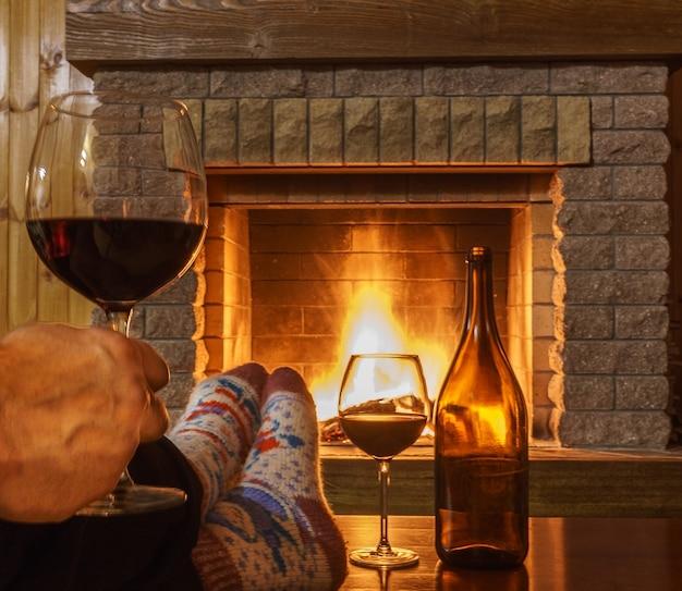 Kieliszek czerwonego wina w męskiej dłoni przed przytulnym kominkiem.