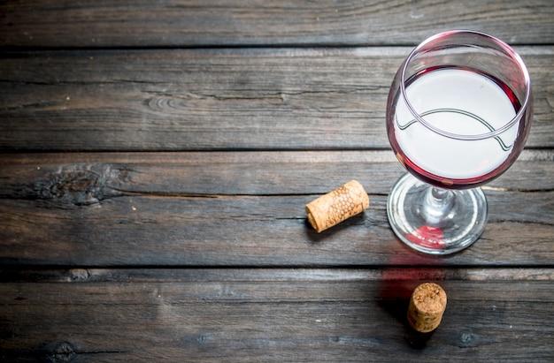 Kieliszek czerwonego wina z korkami na drewnianym stole.