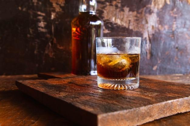 Kieliszek do alkoholu i karafka na drewnianym stole