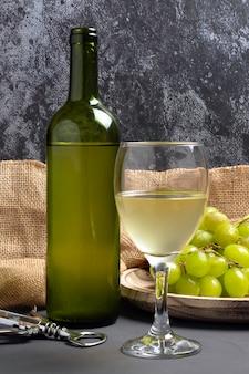 Kieliszek do białego wina z winogronami w piwnicznej atmosferze