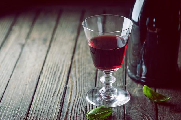 Kieliszek do czerwonego wina i butelka na ciemnym drewnianym tle