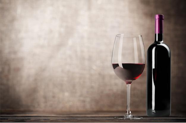 Kieliszek do czerwonego wina i butle na tle drewnianego biurka
