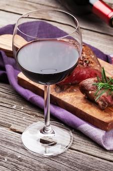 Kieliszek do czerwonego wina i grillowany stek wołowy z rozmarynem, solą i pieprzem na drewnianym stole