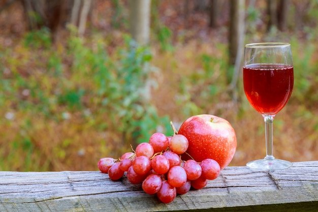 Kieliszek do czerwonego wina i kiść winogron na drewnianym stole przed winnicą w lecie