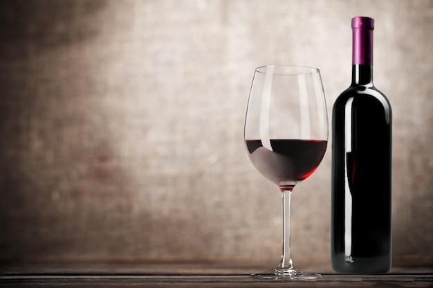 Kieliszek do czerwonego wina na drewnianym biurku na tle ściany