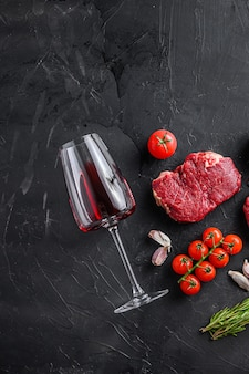 Kieliszek do czerwonego wina w pobliżu surowego steku wołowego na czarnym teksturowanym stole, widok z góry.