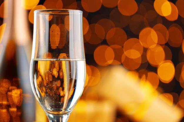 Kieliszek do szampana na niewyraźnych światłach girlandy