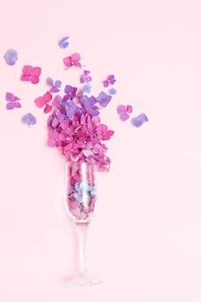 Kieliszek do szampana z wiosennymi kwiatami na różowym tle, koncepcja przyjęcia w minimalnym sezonie. idea rozkwitu natury. fioletowe i różowe kwiaty