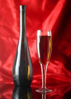 Kieliszek do wina czerwonego i butelka na czerwono