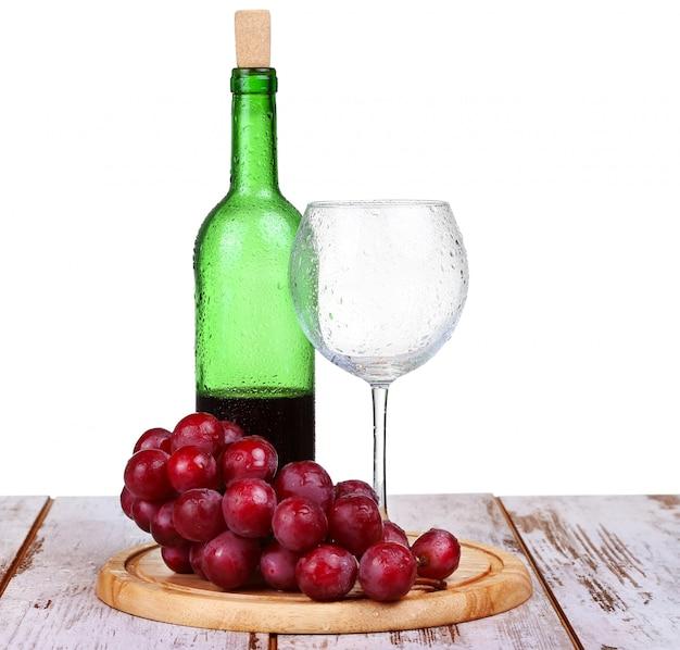Kieliszek do wina czerwonego wina, butelka wina i winogron izolowanych na białym tle