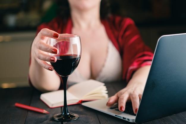 Kieliszek do wina czerwonego wina i laptopa