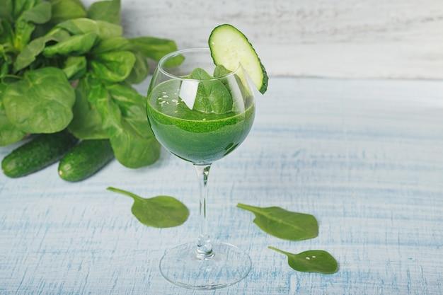 Kieliszek do wina wypełniony koktajlem ze świeżego zielonego szpinaku i ogórka na jasnoniebieskim tle drewnianych. napoje bezalkoholowe. zdrowa żywność i koncepcja wegetariańska.