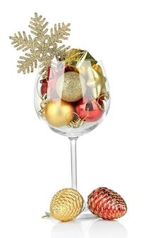 Kieliszek do wina wypełniony ozdobami świątecznymi, na białym tle