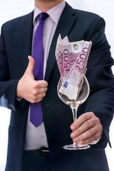 Kieliszek do wina z banknotami euro w męskich rękach