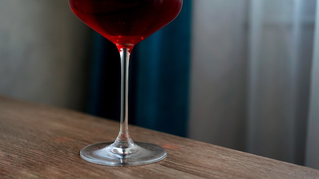 Kieliszek do wina z długimi nóżkami z czerwonym winem wewnątrz rozmytym tłem