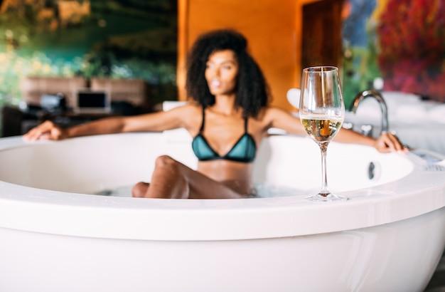 Kieliszek do wina z kobietą relaksującą w wannie z hydromasażem