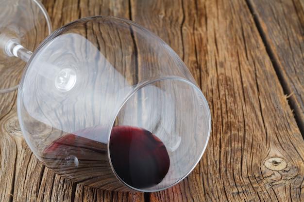 Kieliszek do wina z kroplą czerwonego wina leżał na stole