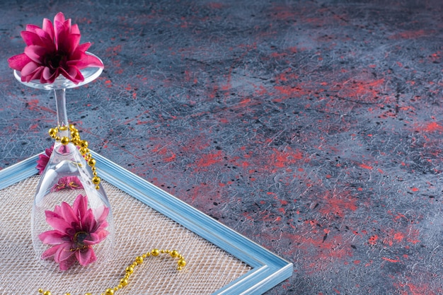 Kieliszek do wina z różowymi kwiatami i żółtym naszyjnikiem na ramie.
